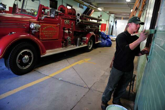 Bridgeport firefighter Jesse Seto puts a fresh coat of paint on the old Engine 10 Firehouse on Putnam Street in Bridgeport, Conn. Friday, Jan. 18, 2013. The firefighters are volunteering their time and labor to restore the 100-year-old building, which until it was decommissioned in 2007 was the oldest firehouse in Bridgeport. Photo: Autumn Driscoll / Connecticut Post