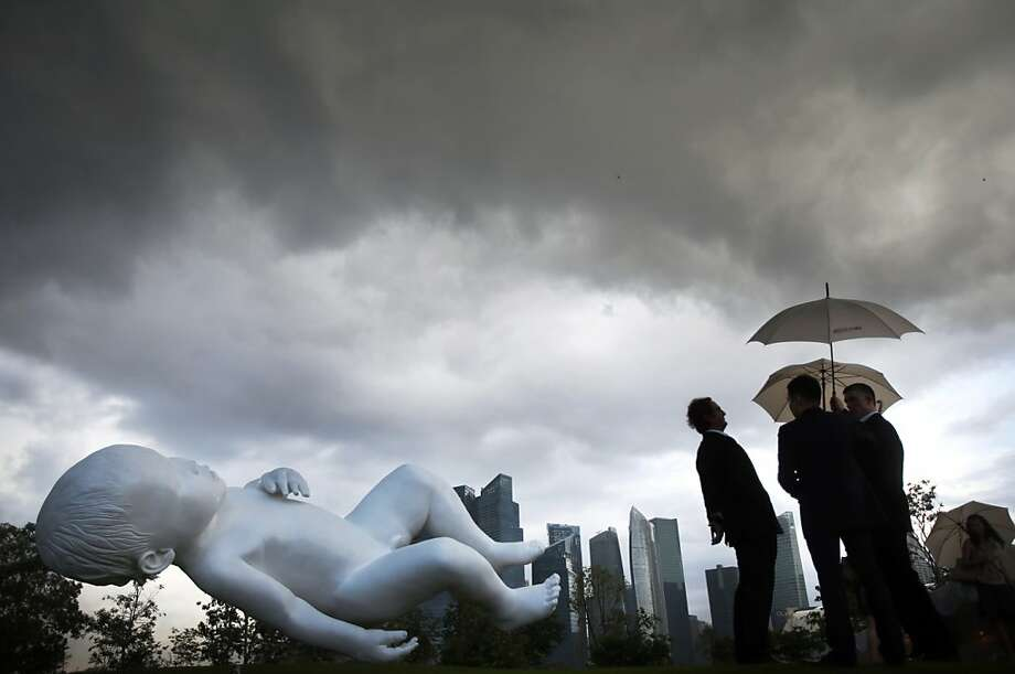"Gentlemen chat in the rain at Singapore's Gardens By The Bay oblivious to the giant white baby floating in their direction. Marc Quinn's bronze and steel sculpture, titled ""Planet,"" is meant to give the illusion of being weightless and suspended in mid-air. Photo: Wong Maye-E, Associated Press"
