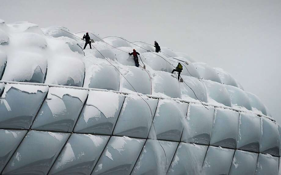 Climbers scale the roof of the FC Bayern Munich stadium in Munich in order to clear snow. Photo: Joerg Koch, Associated Press
