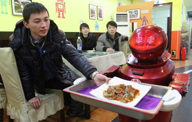 Robot waiters deliver the dishes, running along tracks in the floor. Photo: AFP, AFP/Getty Images / 2013 AFP
