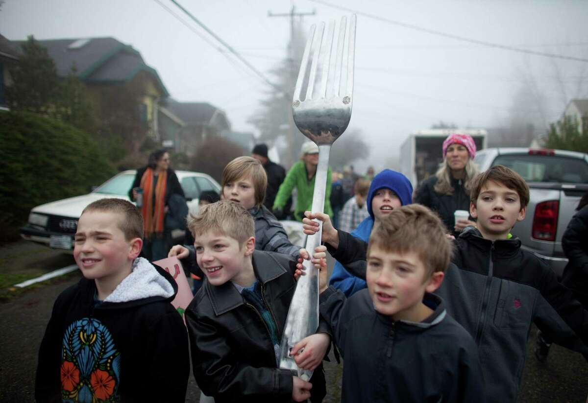 Students from Orca K-8 School carry a giant fork as part of a food drive as they march through Columbia City to honor Martin Luther King, Jr. on Friday, January 18, 2013. The students marched to Columbia Plaza where they participated in a food drive and fund raiser. The federal holiday recognizes the birthday of the civil rights leader. The holiday was first recognized by Ronald Reagan in 1983 but wasn't observed in all 50 states until 2000.