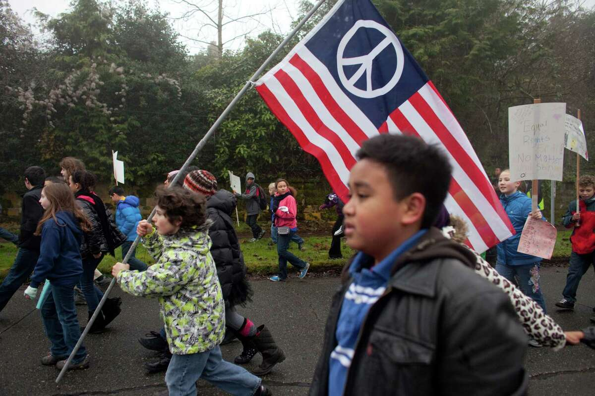 Students from Orca K-8 School march through Columbia City to honor Martin Luther King, Jr. on Friday, January 18, 2013. The students marched to Columbia Plaza where they participated in a food drive and fund raiser. The federal holiday recognizes the birthday of the civil rights leader. The holiday was first recognized by Ronald Reagan in 1983 but wasn't observed in all 50 states until 2000.