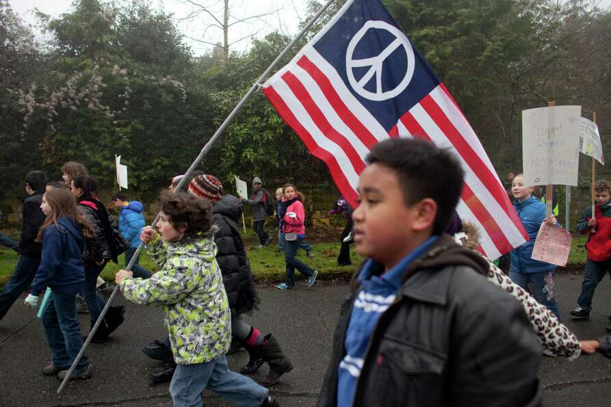 Students from Orca K-8 School march through Columbia City to honor Martin Luther King, Jr. on Friday