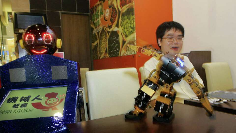 A robot waiter (left) takes orders, and then another robot dances to entertain waiting diners.