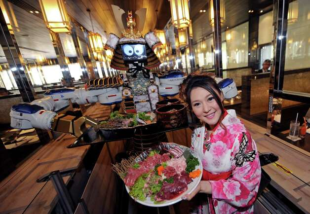 A robot waiter and restaurant owner Lapassarada Thanapanth hold trays of food at a Japanese robot restaurant in Bangkok, Thailand on April 1, 2010. Photo: PORNCHAI KITTIWONGSAKUL, AFP/Getty Images / 2010 AFP