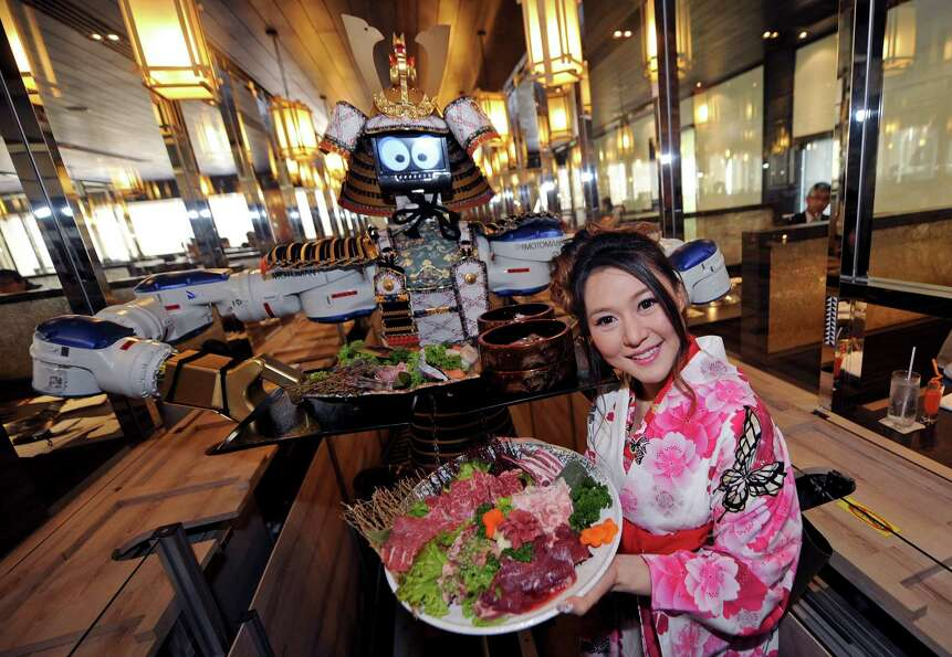 A robot waiter and restaurant owner Lapassarada Thanapanth hold trays of food at a Japanese robot re