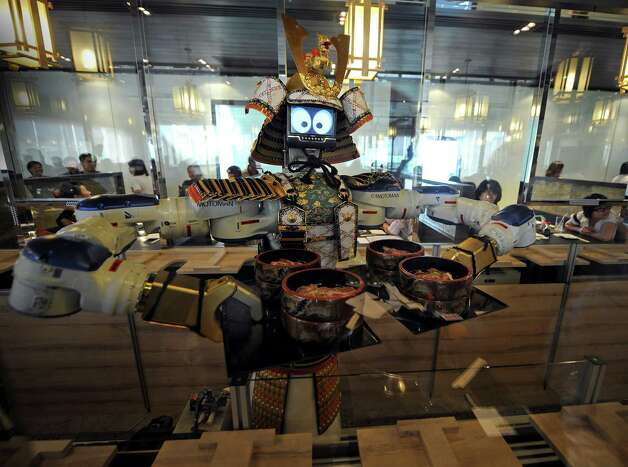 Robots don't cook the food, but they do serve it, collect empty plates and dance. Photo: PORNCHAI KITTIWONGSAKUL, AFP/Getty Images / 2010 AFP