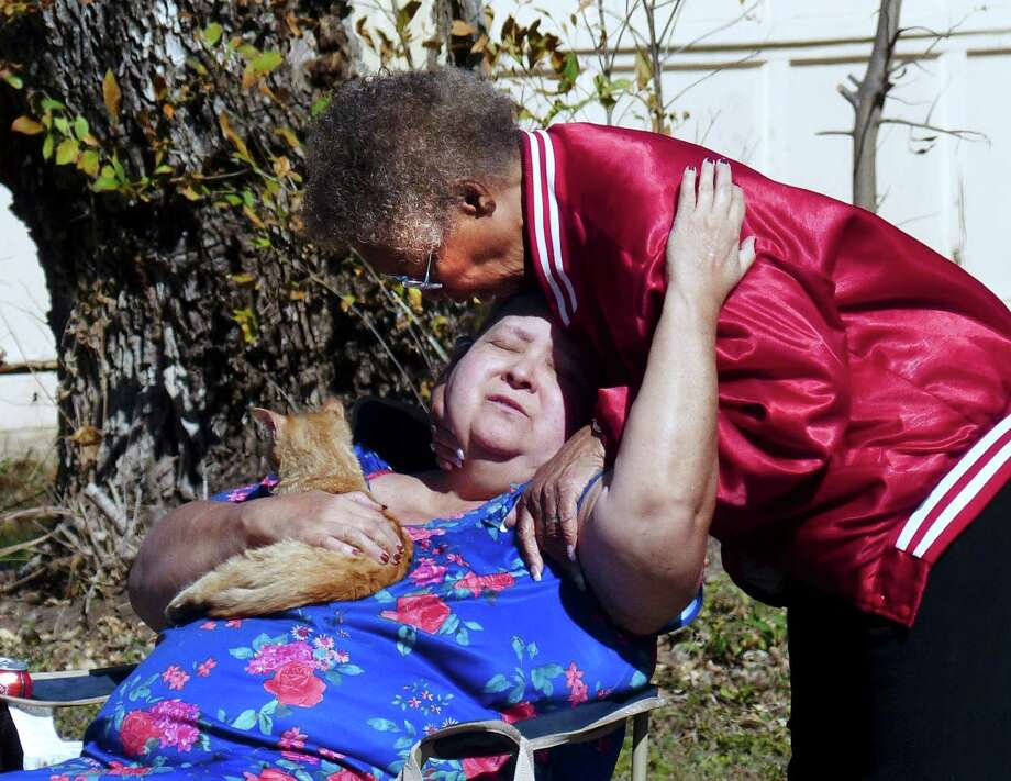Gloria Robinson, standing, offers comfort to her neighbor after her house burned, causing the deaths of several of her pet cats in the 3400 block of Chateau Drive on Friday, Jan. 18, 2013. Firefighters said 17 cats and two dogs were in the house, along with its occupants. Photo: Billy Calzada, Billy Calzada/Express-News / SAN ANTONIO EXPRESS-NEWS