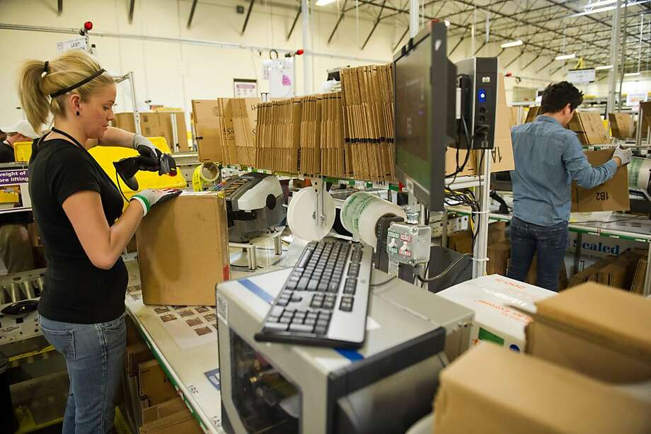 Alexis Debroeck scans an Amazon shipping box at the online retailer's Phoenix distribution center. Photo: David Paul Morris, Bloomberg