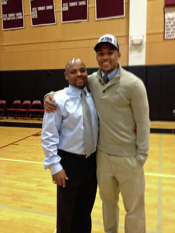 St. Luke's coach Noel Thomas Sr., left, poses with his son Noel Jr., who signed a National Letter of Intent to play football at UConn next fall. Photo: Jon Chik