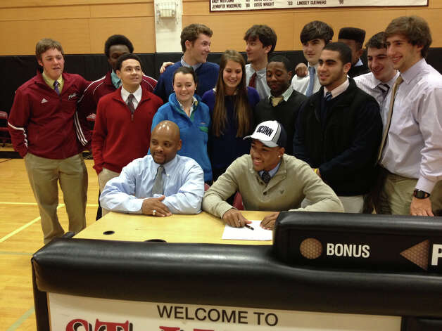 St. Luke's' Noel Thomas smiles as he signs his National Letter of Intent to play football at UConn next fall. Seated next to him is Noel Thomas Sr., his father and St. Luke's head football coach. Photo: Jon Chik