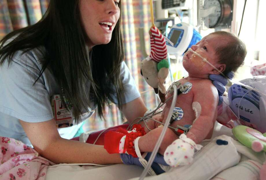 Physical Therapist Courtney Collins works with Audrina Cardenas to reach certain physical milestones that babies her age reach at Texas Children's Hospital on Thursday, Dec. 13, 2012, in Houston. Audrina Cardenas was born with a third of her heart growing outside her chest, a condition called ectopia cordis. Approximately, 90 percent of the infants born with this condition are either stillborn or die shortly after birth. Those who survive are often subject to stunted, abbreviated lives. Audrina has survived 3 months, making her the longest recorded survivor in Texas. Photo: Mayra Beltran, Houston Chronicle / © 2012 Houston Chronicle