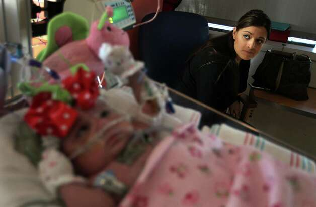 Ashley Cardenas anxiously views a TV monitor showing Audrina Cardenas' vital signs at Texas Children's Hospital on Thursday, Dec. 13, 2012, in Houston.  Photo: Mayra Beltran, Houston Chronicle / © 2012 Houston Chronicle