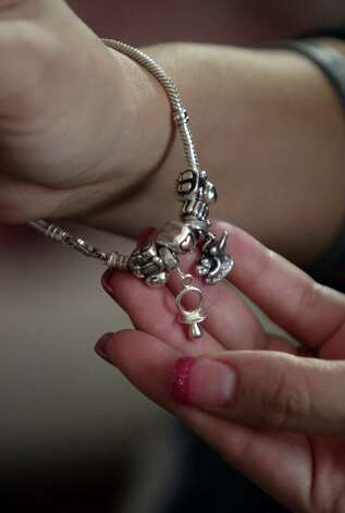 Ashley Cardenas wears a charm bracelet representing her children, and the tiny pacifier represents daughter Audrina Cardenas who is recovering at Texas Children's Hospital on Thursday, Dec. 13, 2012, in Houston.  Audrina Cardenas was born with a third of her heart growing outside her chest, a condition called ectopia cordis. Approximately, 90 percent of the infants born with this condition are either stillborn or die shortly after birth. Those who survive are often subject to stunted, abbreviated lives. Audrina has survived 3 months, making her the longest recorded survivor in Texas. Photo: Mayra Beltran, Houston Chronicle / © 2012 Houston Chronicle