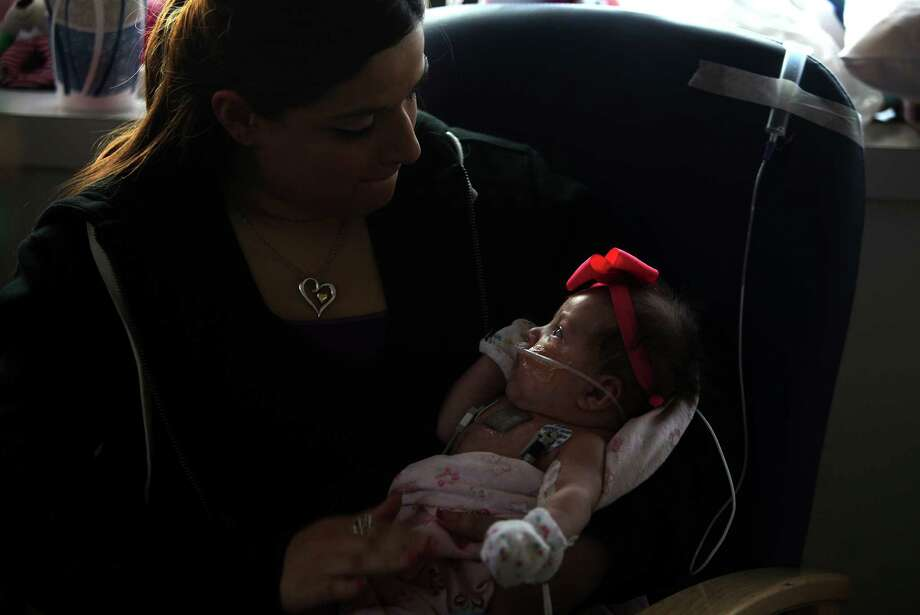 Ashley Cardenas holds her daughter Audrina Cardenas as vents the feeding tube at Texas Children's Hospital on Friday, Dec. 28, 2012. Photo: Mayra Beltran, Houston Chronicle / © 2012 Houston Chronicle