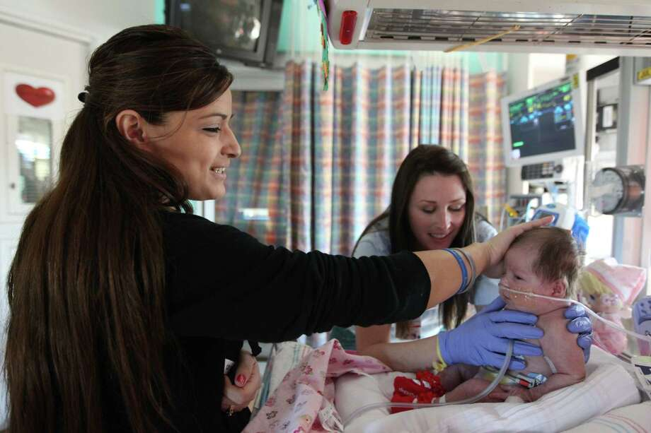 Ashley Cardenas caresses daughter Audrina Cardenas as physical therapist Courtney Collins works with the baby to develop strength . Photo: Mayra Beltran, Houston Chronicle / © 2012 Houston Chronicle