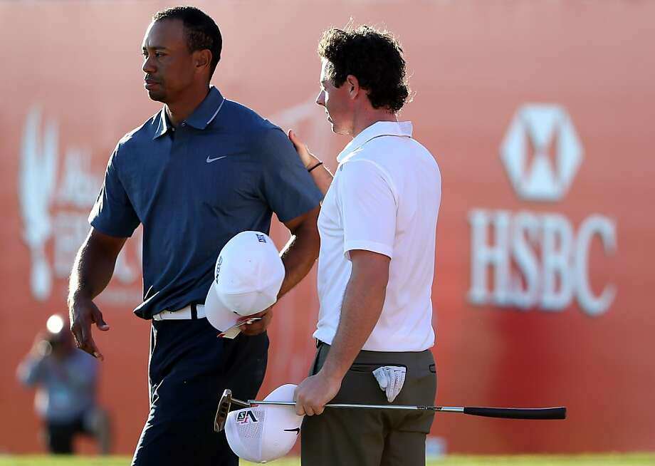 Tiger Woods and Rory McIlroy walk No. 18, where their tournament ended. Photo: Ross Kinnaird, Getty Images