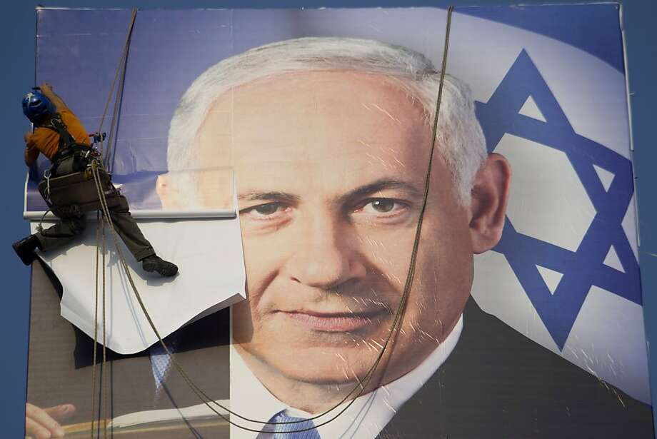 A political poster of Premier Benjamin Netanyahu is put up in Tel Aviv ahead of Tuesday's election. Photo: Ariel Schalit, Associated Press