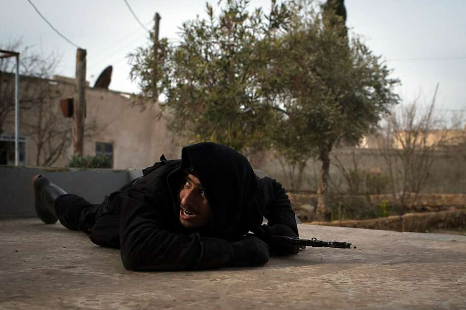 "A Rebel fighter ducks for cover from government jet fighters in the city of Aleppo on January 18, 2013. UN leader Ban Ki-moon warned that Syria is in a ""death spiral"", as his top humanitarian and human rights officials pleaded with the UN Security Council to take firmer action. Photo: Elias Edouard, AFP/Getty Images"