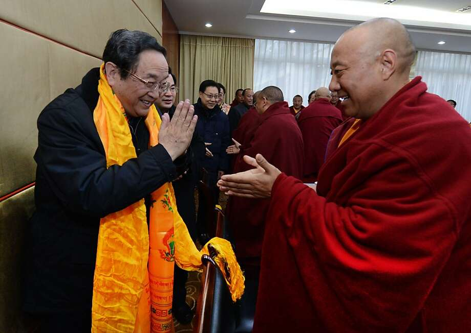 In this Jan. 8, 2013 photo released by China's Xinhua News Agency, Yu Zhengsheng, left, a Standing Committee member of the Political Bureau of the Communist Party of China (CPC) Central Committee, is greeted by a participant during a seminar held with Tibetan Buddhist representatives in Ganzi Tibetan Autonomous Prefecture, southwest China's Sichuan Province. Yu visited Ganzi at the center of the self-immolations, urging Buddhist clergy to be patriotic and denouncing the Dalai Lama. Chinese authorities are responding to an intensified wave of Tibetan self-immolation protests against Chinese rule by clamping down even harder ? criminalizing the suicides, arresting protesters' friends and even confiscating thousands of satellite TV dishes. (AP Photo/Xinhua, Ma Zhancheng) NO SALES Photo: Ma Zhancheng, Associated Press