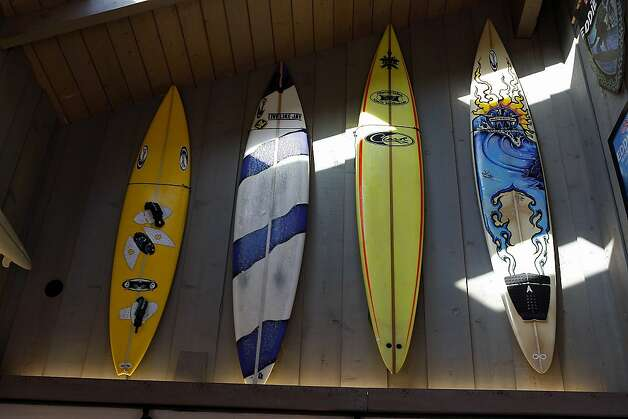 Several surfboards hang on the wall at Mavericks Surf Shop. Photo: Sean Havey, The Chronicle