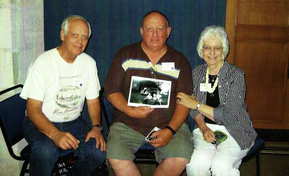 Now: Summer 2010, Bill Gros, Albert Karnowski and Theresa Gros Gold, at Hoelscher-Buxkemper Family Reunion in New Braunfels. Bill lives in Baton Rouge, Albert in Boise, Ida., and Theresa in San Antonio. Albert holds a copy of a 1944 photo of the three of them as children. Photo: Gold, Reader Submission