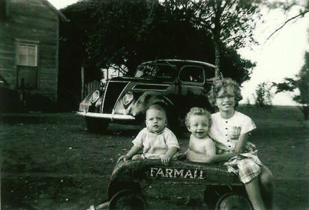 Summer 1944, Bill Gros, Albert Karnowski and Theresa Gros at Karnowski grandparents' place in Violet, Tex., for a family reunion. Bill and Theresa lived in San Antonio; Albert lived in Boise, Ida. Bill and Theresa are brother and sister; Albert is a first cousin. All are grandchildren of Frank Karnowski and Emma Hoelscher Karnowski. That's a Farmall wagon they're sitting in with a 1930s Ford in background Photo: Gold, Reader Submission
