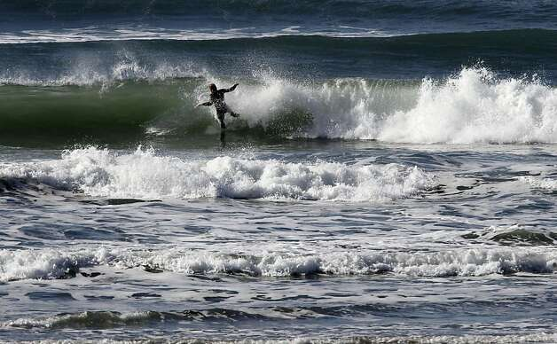 A surfer hits the water off Ocean Beach on Friday Jan. 18,  2013,  in San Francisco, Calif. Expects are reporting that swells will increase through the weekend posing dangers to people enjoying the coastline. Photo: Michael Macor, The Chronicle