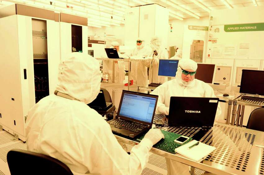 Jesse Lyons, field service engineer for Applied Materials, right, works on his laptop in a clean room on Friday, Jan. 18, 2013, at Albany NanoTech in Albany, N.Y. (Cindy Schultz / Times Union)