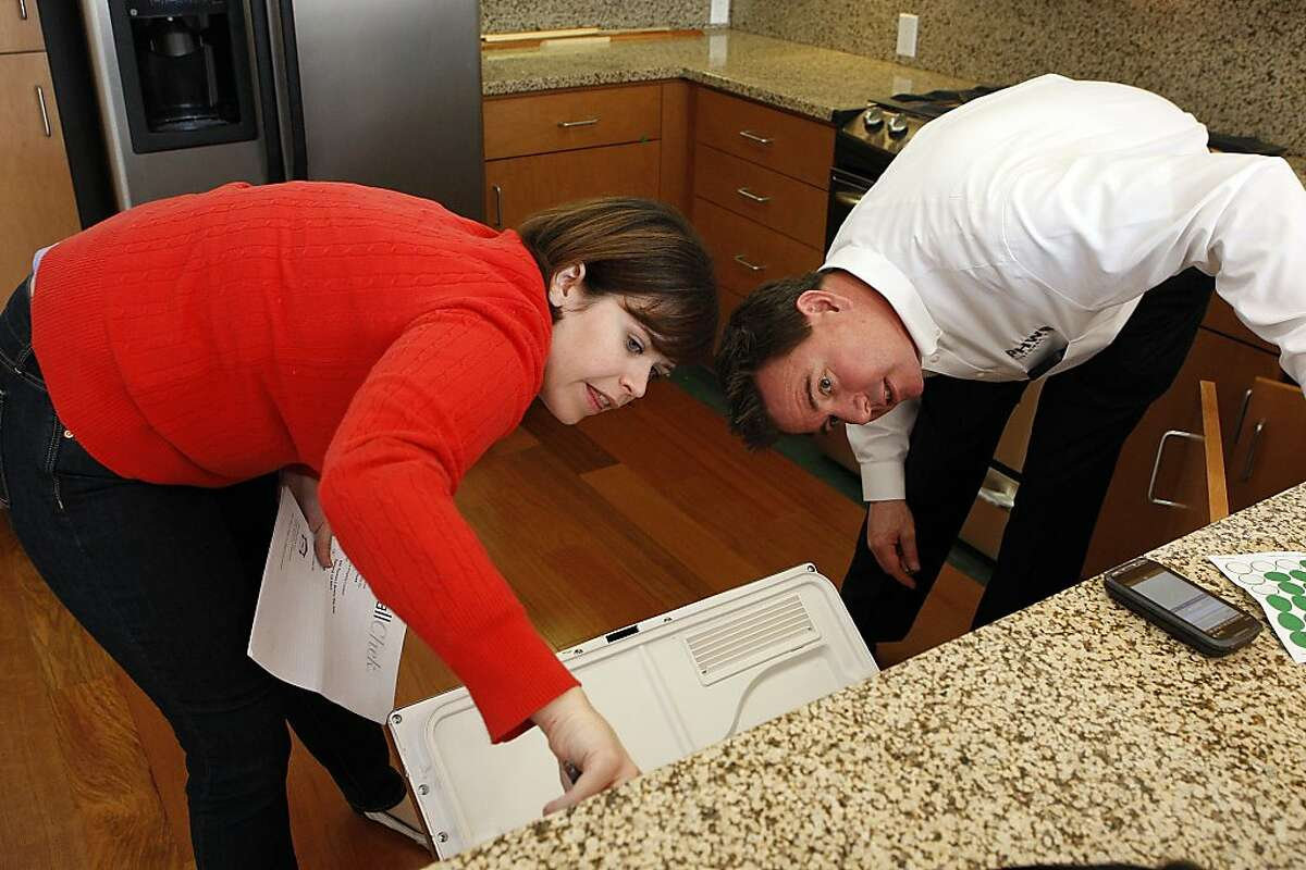 First-time homeowner Beth Hood points out a possible recall item on a dishwasher with third-party customer service representative, Jason Wilson, as they go down the list of small improvements that need to be made before Hood moves into her new condominium at the Uptown Place complex on January 16, 2013 in Oakland, Calif. With prices rising for single-family homes, condos seem to be an affordable alternative for both home buyers and investors.
