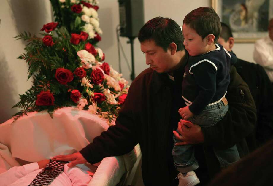 Family and friends of Rey Dorantes attend his wake on January 17, 2013 in Chicago, Illinois. Fourteen-year-old Dorantes died after being shot 6 times while he was sitting on the front porch of his home on January 11. Dorantes' murder was the 21st homicide recorded in Chicago for 2013, a city which saw more than 500 homicides in 2012. Photo: Scott Olson, Getty Images / 2013 Getty Images