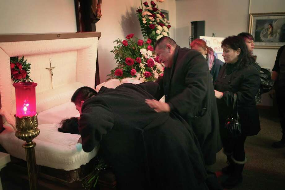 Esteban Dorantes (L), the father of Rey Dorantes, is comforted by his brother Martin during his son's wake on January 17, 2013 in Chicago, Illinois. Fourteen-year-old Rey Dorantes died after being shot 6 times while he was sitting on the front porch of his home while talking on the phone on January 11. Dorantes' murder was the 21st homicide recorded in Chicago for 2013, a city which saw more than 500 homicides in 2012. Photo: Scott Olson, Getty Images / 2013 Getty Images