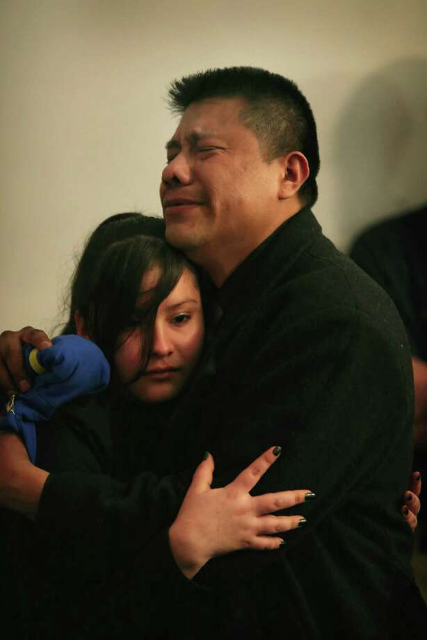 Esteban Dorantes (R), the father of Rey Dorantes, is comforted at his son's wake on January 17, 2013 in Chicago, Illinois. Fourteen-year-old Rey Dorantes died after being shot 6 times while he was sitting on the front porch of his home while talking on the phone on January 11. Dorantes' murder was the 21st homicide recorded in Chicago for 2013, a city which saw more than 500 homicides in 2012. Photo: Scott Olson, Getty Images / 2013 Getty Images