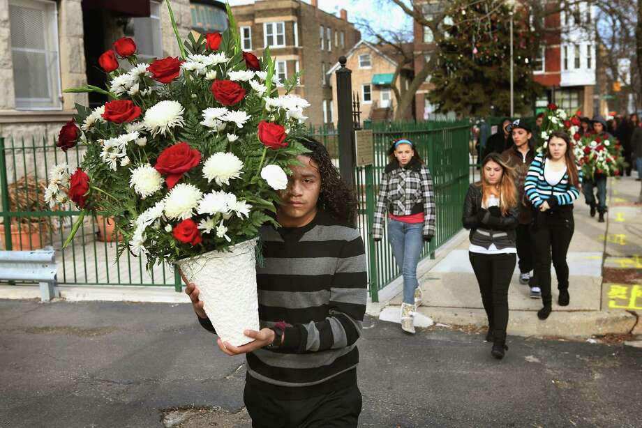 Jonathan Dorantes carries flowers home from the church following a funeral mass for his brother Rey on January 18, 2013 in Chicago, Illinois. Rey Dorantes, 14, died after being shot six times while he was sitting on the front porch of his home while talking on the phone on January 11. Dorantes's murder was the 21st homicide recorded in Chicago for 2013, a city which saw more than 500 homicides in 2012. Photo: Scott Olson, Getty Images / 2013 Getty Images