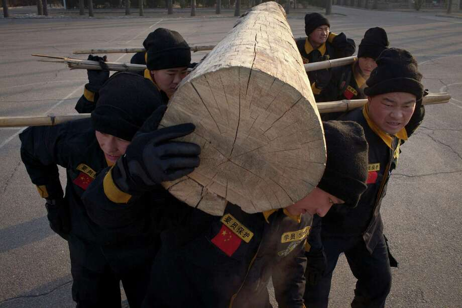 Trainees of a bodyguard camp carry a log during their fitness training at the Genghis Security Academy in Beijing. The academy is one of several bodyguard schools in China that offer protection for the country's growing number of wealthy businessmen and women, but in its case, the focus is on the international market. Photo: Alexander F. Yuan, Associated Press / AP