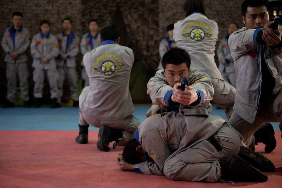Trainee bodyguards perform an exercise at the Genghis Security Academy in Beijing. In sub-zero winter cold, trainees at an army base outside Beijing wake before dawn to practise martial arts and evasive driving, under the instruction of a Portuguese ex-special forces soldier. Photo: ED JONES, AFP/Getty Images / AFP