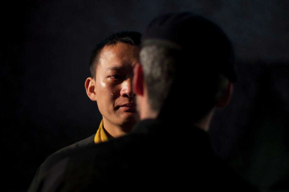 A trainee of a bodyguard camp sheds tears as he is briefed on his performance after the day's training by a coach at the Genghis Security Academy in Beijing. Photo: Alexander F. Yuan, Associated Press / AP