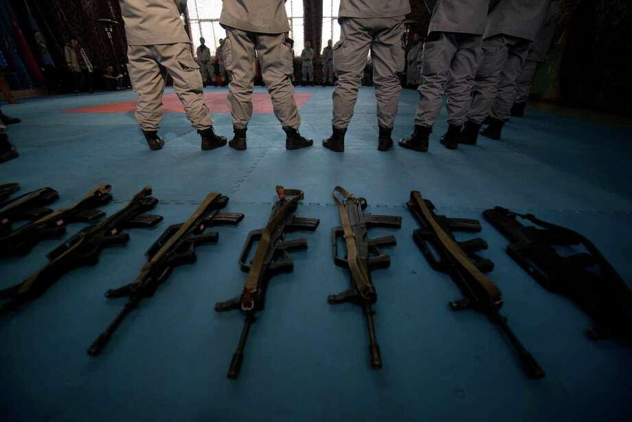 Assault rifles lie at the feet of bodyguard trainees at the Genghis Security Academy in Beijing on January 17, 2013. Photo: ED JONES, AFP/Getty Images / AFP