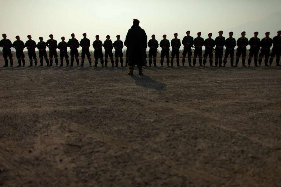 Chen Yongqing, center, manager of Tianjiao Special Guard & Security Consultant Co., speaks to a group of trainees after a training session with assault rifles at the Genghis Security Academy in Beijing Friday, Jan. 18, 2013. Photo: Alexander F. Yuan, Associated Press / AP