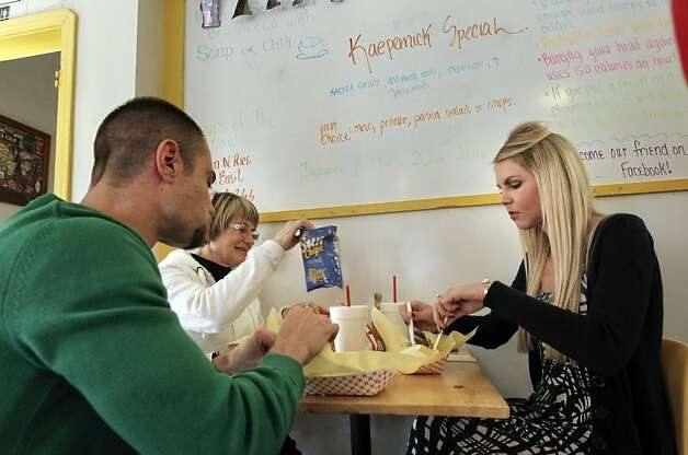 Above, Lindsay Kaepernick (right) eats a Kaepernick Special at Footers with Justin Smernes and his mother, Debra. The Kaepernick Special, left, comes with chili, jalapenos and cole slaw. Photo: Michael Macor, The Chronicle