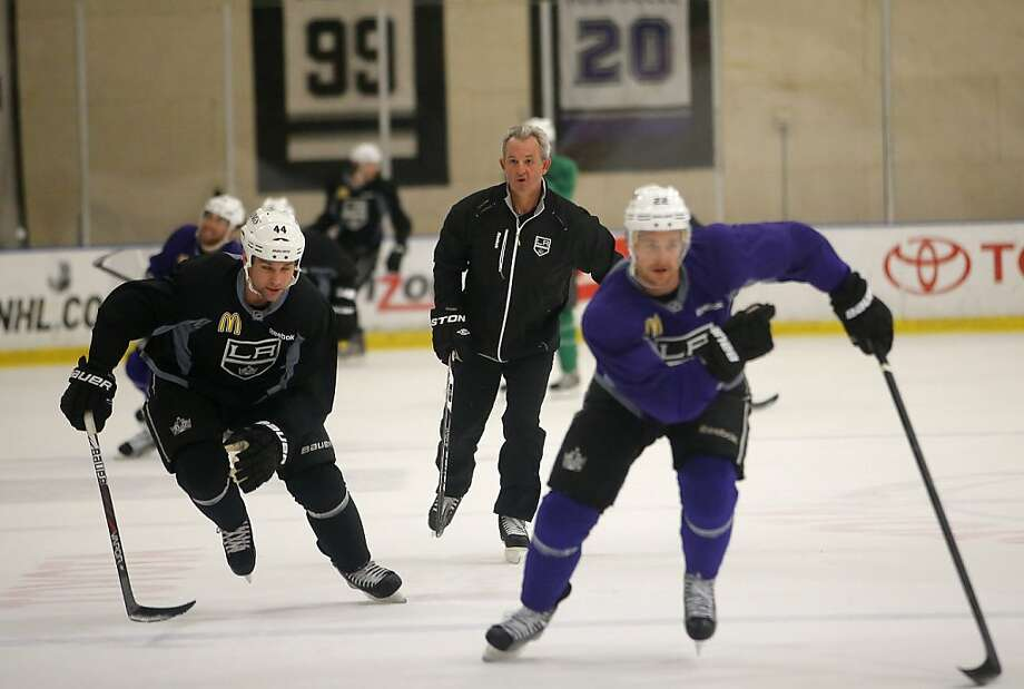 Darryl Sutter (center) watches Davis Drewiske (left) and Trevor Lewis skate in preparation for the Kings' opener of the lockout-shortened NHL season against the Blackhawks on Saturday. Photo: Jae C. Hong, Associated Press