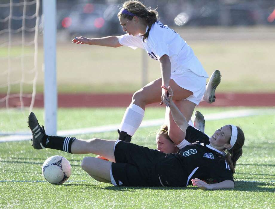 Kingwood Park forward Sarah Flottman (9) collides with Ridge Point midfielder Zoey Pawlik (21) and goalie Meghan Brady as she dives for the ball during a high school girls soccer game at the I-10 Shootout at Mayde Creek High School, Thursday, Jan. 17, 2013, in Houston. Kingwood Park tied Ridge Point at one goal apiece. (AP Photo/The Courier, Jason Fochtman) Photo: Jason Fochtman, Associated Press / Conroe Courier