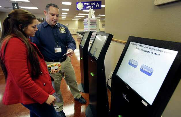 Enrique Antu helps Danielle Jimenez, left, at an automated kiosk at the Department of Public Safety new Leon Valley Mega Center. Photo: Bob Owen, San Antonio Express-News / ©2013 San Antonio Express-News
