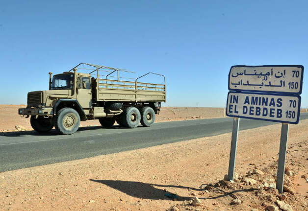 An Algerian military truck drives past a road sign indicating the city of Ain Amenas where hostages have been kidnapped by Islamic militants at a gas plant, Friday, Jan. 18, 2013.