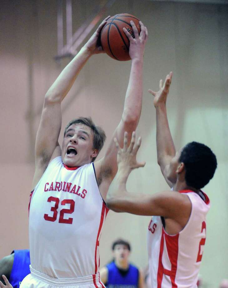 Alex Wolf # 32 of Greenwich grabs a rebound during the boys high school basketball game between Greenwich High School and Darien High School at Greenwich, Friday night, Jan. 18, 2013. At right is Wolf's teammate C.J. Byrd. Photo: Bob Luckey / Greenwich Time