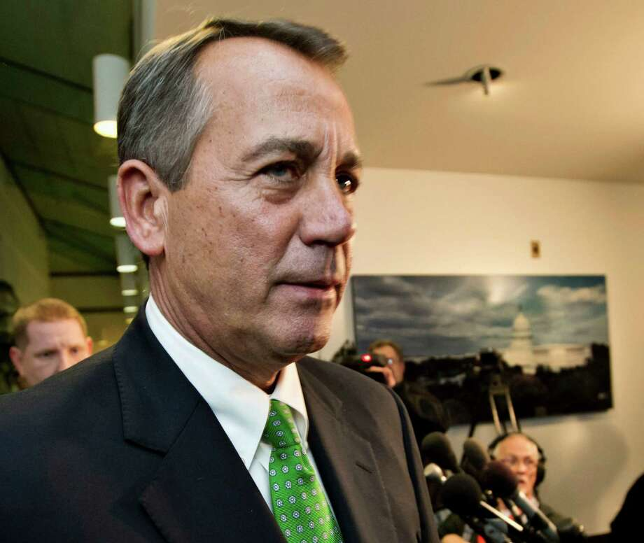 FILE - This Jan. 1, 2013 file photo shows House Speaker John Boehner of Ohio walkig past reporters after a closed-door meeting meeting of House Republicans on Capitol Hill in Washington. The GOP-controlled House will vote next week to permit the government to borrow more money to meet its obligations, a move aimed at heading off a market-rattling confrontation with President Barack Obama over the so-called debt limit. Full details aren't settled yet, but the measure would give the government about three more months of borrowing authority beyond a deadline expected to hit as early as mid-February, a Republican official said Friday.   (AP Photo/J. Scott Applewhite, File) Photo: J. Scott Applewhite