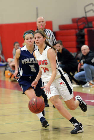New Canaan's Colette Pellegrini (14) controls the ball as Staples' Ali April (5) defends during the girls basketball game at New Canaan High School on Friday, Jan. 18, 2013. Photo: Amy Mortensen / Connecticut Post Freelance
