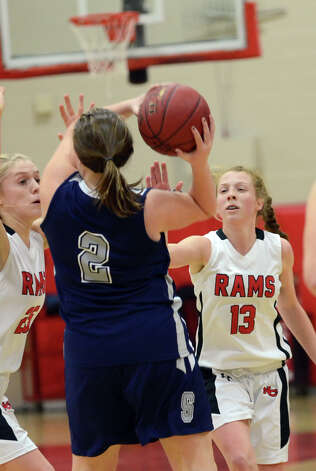 New Canaan's Kelly Armstrong (25) and Elizabeth Miller (13) put the pressure on Staples' Maggie Fair (2) during the girls basketball game at New Canaan High School on Friday, Jan. 18, 2013. Photo: Amy Mortensen / Connecticut Post Freelance