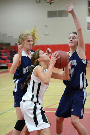 New Canaan's Colette Pellegrini (14) attempts a shot as Staples' Nikki Bukovsky (22) and Madeline Schemel (22) defend during the girls basketball game at New Canaan High School on Friday, Jan. 18, 2013. Photo: Amy Mortensen / Connecticut Post Freelance
