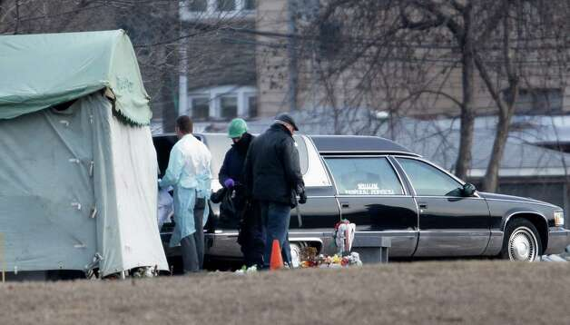 Workers at Rosehill Cemetery in Chicago on Friday, Jan. 18, 2013, place the body of Urooj Khan into a hearse after it was exhumed for an autopsy to help solve the mystery surrounding his death. Khan, 46, who was poisoned with cyanide after winning the lottery, died in July as he was about to collect $425,000 in winnings. His death was initially ruled a result of natural causes, but a relative pressed for a deeper look and his death was reclassified as a homicide.  (AP Photo/M. Spencer Green) Photo: M. Spencer Green